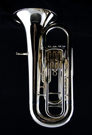 brass band: A complete brass gold bass tuba euphonium against a black background in the vertical format with copy space. Stock Photo