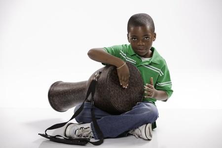 小さな孤立したアフリカ系アメリカ人男性の子白い背景に対してジャンベ ドラムを再生する方法を勉強して緑のシャツで。