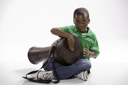 A small isolated African American male child in a green shirt studying how to play a djembe drum against a white background. Stock Photo