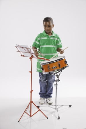 A small isolated African American male child in a green shirt studying how to play a snare drum against a white background. photo