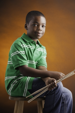 A small isolated African American male child  in a green shirt sitting on a wood stool holding drumsticks and smiling against an orange background. photo