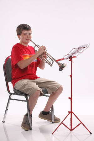 facing right: A male early teenage boy child playing trumpet facing to the right isolated against a white background with copy space in the vertical format. Stock Photo