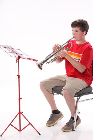 男性に早期 10 代の少年子供は、垂直方向の形式でコピー スペースで白い背景に対して隔離される左に直面しているトランペットを演奏します。