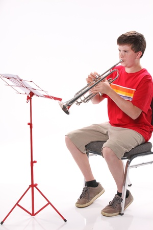 performers: A male early teenage boy child playing trumpet facing to the left isolated against a white background with copy space in the vertical format.