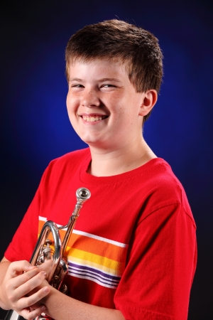 A male early teenage boy child holding trumpet facing to the left isolated against a spotlight blue black background with copy space in the vertical format. photo