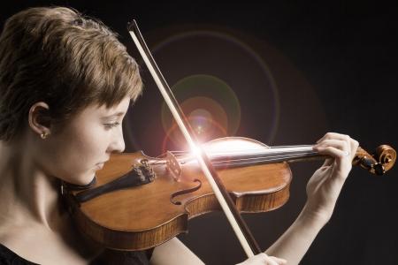 violines: Intenso adolescente femenino con el pelo rojo marrón aislado que toca el violín con el fondo negro Foto de archivo