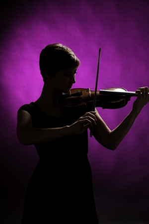 Silhouette of a teenage female girl with red brown hair and violin or viola isolated on a pink background