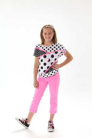 elementary age girl: Ten year old female girl in pink with hand on hip smiling isolated against a white background with copy space in the vertical format.