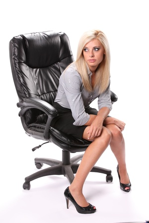 A thinking business woman sitting facing front in a black knee length skirt and high heels isolated on white.