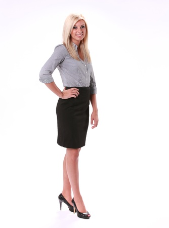 A smiling business woman stand facing front in a black knee length skirt and high heels isolated on white. photo