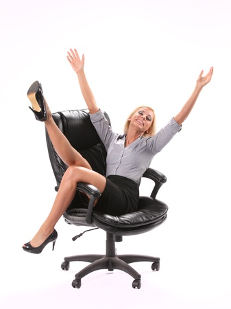 swivel: A excited business woman sitting in a swivel chair with her legs and hands up in the air isolated on white in the vertical format. Stock Photo