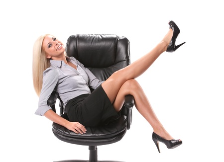 swivel: A happy business woman sitting in a swivel chair with her legs up in the air isolated on white.