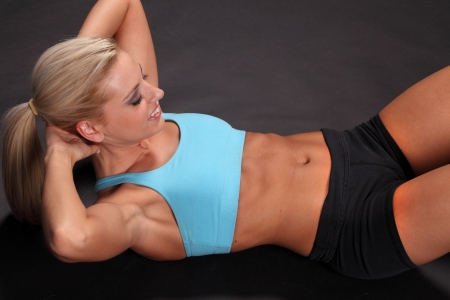 situps: An attractive young female woman in black shorts and blue top training or working out by doing sit-ups isolated against a black background. Stock Photo