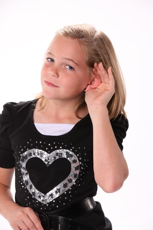 preteen: Preteen 10 year old female girl listening or hearing isolated against a white background. Stock Photo