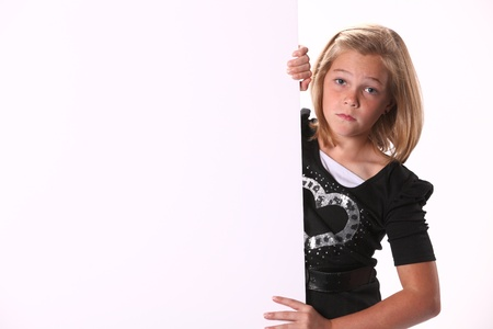 10 year old: Attractive preteen 10 year old female girl holding a white sign isolated against a white background. Stock Photo