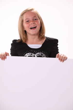 10 year old: Happy smiling attractive preteen 10 year old female girl holding a white sign isolated against a white background.