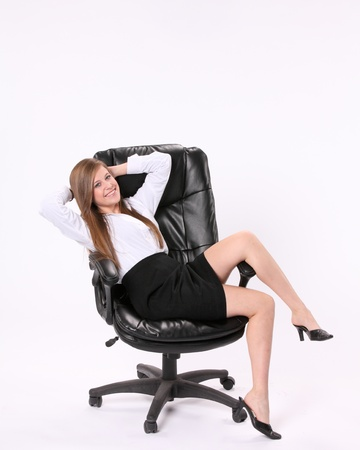 Happy excited secretary sitting cross ways in a swivel chair with her hands behind her head against a white background. Stock Photo - 16524048