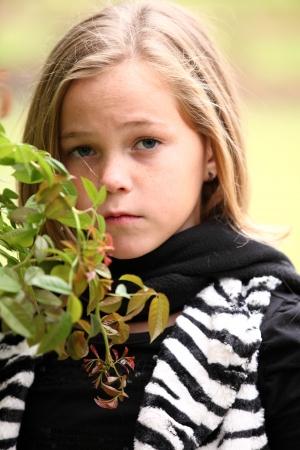 Aantrekkelijke Kaukasische preteen 10-jarige meisje staande naast een groene plant Stockfoto