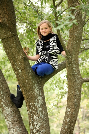 10 year old: Attractive preteen 10 year old female girl climbing around in a tree