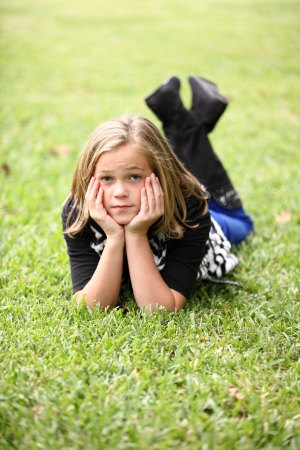 Attractive preteen 10 year old female girl lying on green grass with her face propped up on her hands.  Foto de archivo
