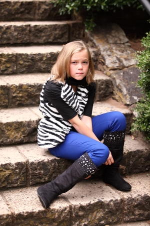 Attractive preteen 10 year old female girl unhappy and sitting on stone steps
