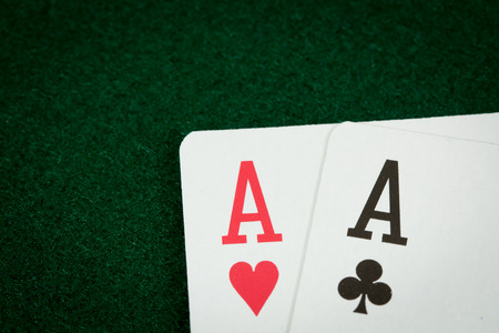 dealt: A close of shot of two aces on a green poker table