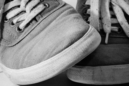 dirty feet: A pair of dirty shoes and feet crossed in black and white Stock Photo