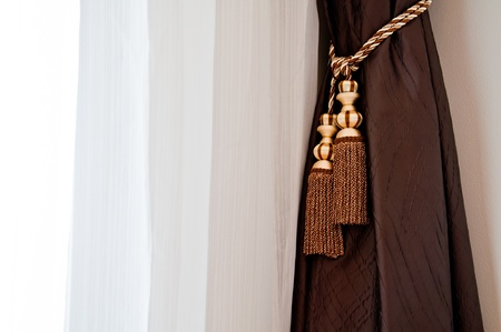 brown and white curtain with the window lighting