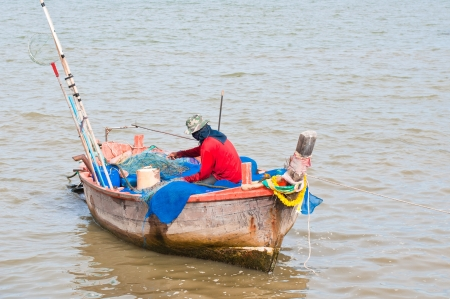 Fisherman mending net in his boat photo