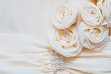 Cream fabrics roses and pearl beads on the dress photo