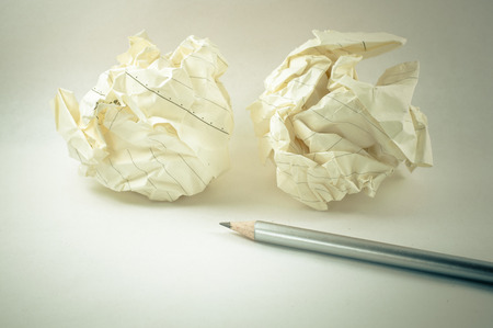 crumpled paper ball: Crumpled paper ball with a pencil in white background