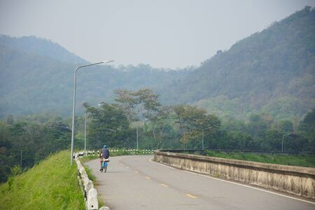 The man  is riding bicycle on the road with mountain background