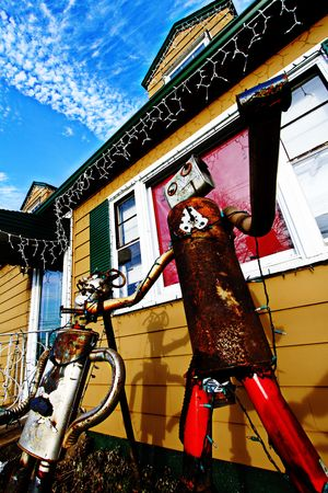 Picture taken in Penndel, Pennsylvania outside of Philadelphia.  Displays two robot statues adorning the front of a yellow house.   photo