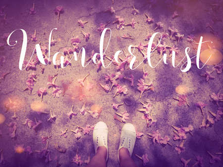 Wanderlust handwriting word on pink flowers fallen on road with woman feet wear white sneakers shoe background