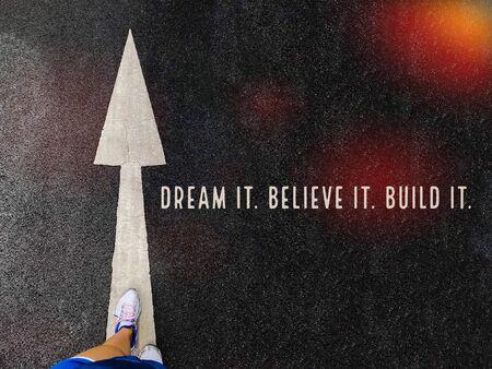 Dream it. Believe it. Build it word on feet wear sport shoe step on white big arrows background Banque d'images