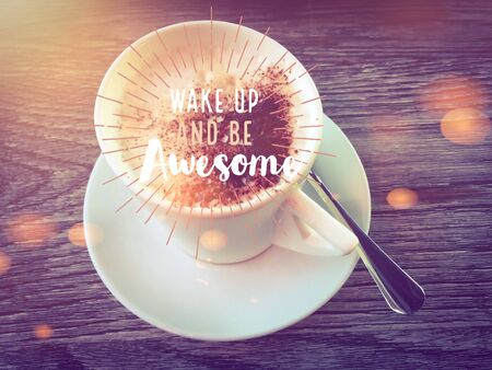Wake up and be awesome word on hot coffee cup on wooden table background bokeh light