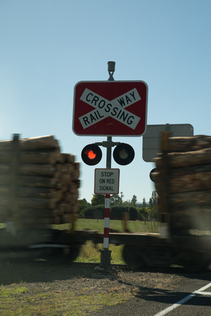 Sign: Railway crossing sign with a train in the backround 版權商用圖片