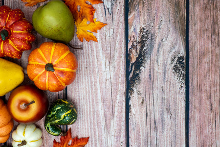 Fall pumpkins, gourds and foliage on a wooden background. Concept for autumn background