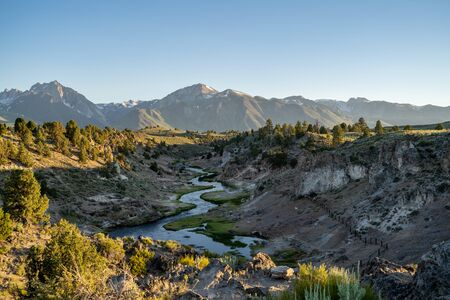 Winding creek of Hot Creek Geological Site in Mammoth Lakes California at dusk sunset, with backlighting. Sierra Nevada mountains in distance