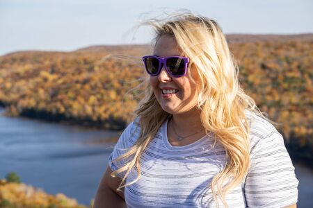 Adorable blonde woman poses at Lake of the Clouds in Porcupine Mountains wilderness state park in Michigan, looking away from camera