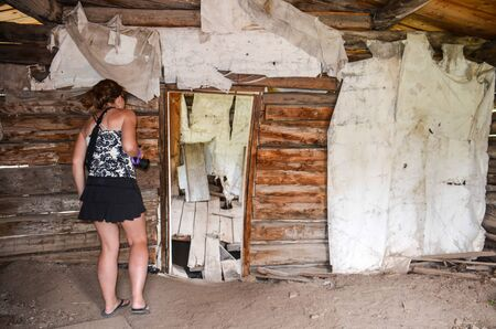 Female urban explorer investigates an abandoned building interior in Miners Delight Wyoming