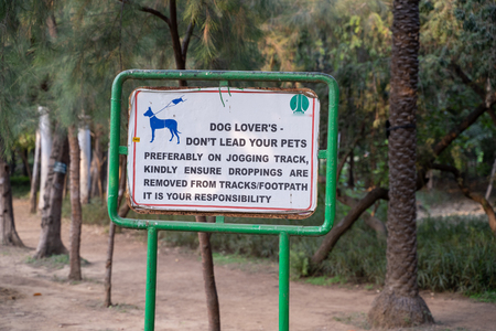 New Delhi, India - November 16, 2019: Sign inside Lodhi Garden, a large city park, reminding dog owners to pick up dog poop