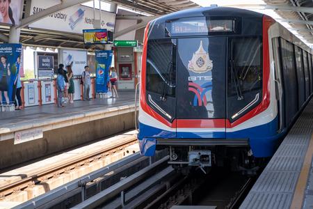 Bangkok, Thailand - November 30, 2019: BTS Skytrain passenger train pulls into the Mo Chit station to pick up commuters