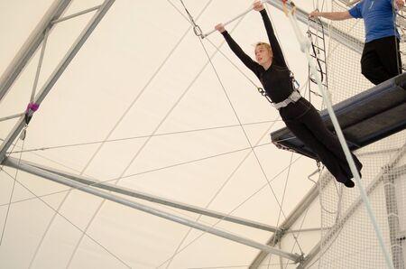 Une femelle adulte est suspendue à un trapèze volant dans une salle de sport intérieure. La femme est une trapéziste amateur.