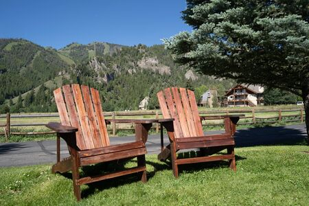 Two empty wood adirondack chairs sit on grass, overlooking the Sawtooth mountains of Idaho. Taken in Ketchum, ID