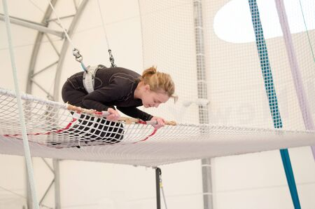 An adult female lands on a net, preparing to dismount at a on a flying trapeze school at an indoor gym. The woman is an amateur trapeze artist.