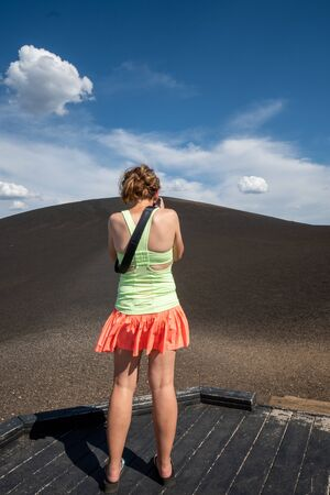 Woman photographer wearing bright clothes photographs the Inferno Cone in Craters of the Moon National Monument 版權商用圖片