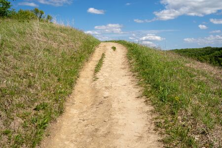 Dirt hiking trail surrounded by green grass goes up a hill on a sunny day, Leading lines Stock Photo - 135256076