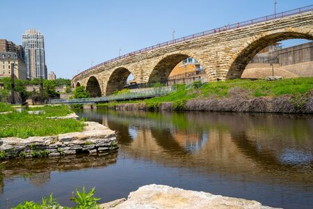 Cityscape scene of downtown Minneapolis, as seen from Mill Ruins Park. View of the Stone Arch bridge on sunny spring day Banque d'images