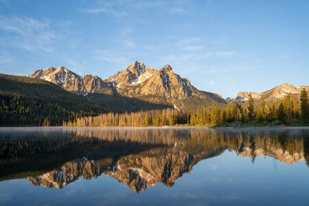Sunrise at Stanley Lake with Sawtooth Mountains reflecting in the calm water